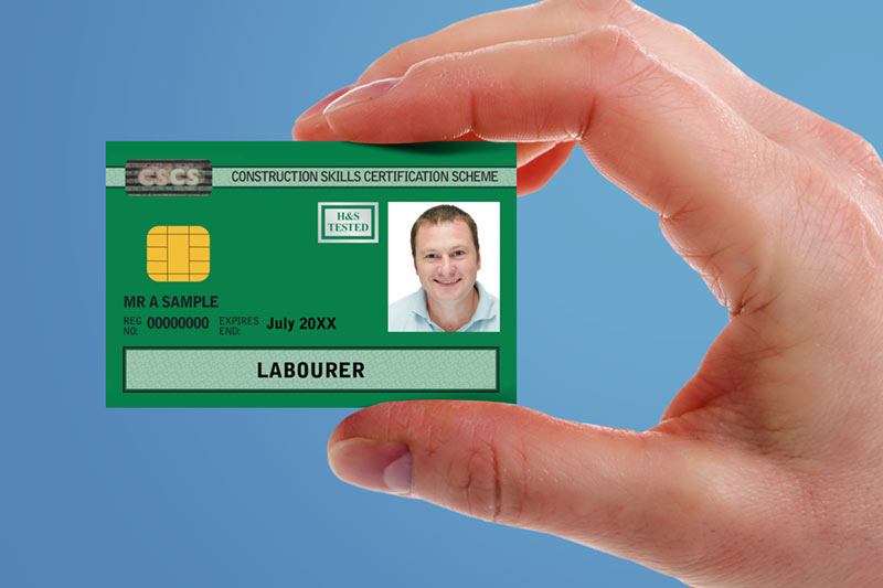 A hand holding a small card that says construction skills certification scheme, labourer