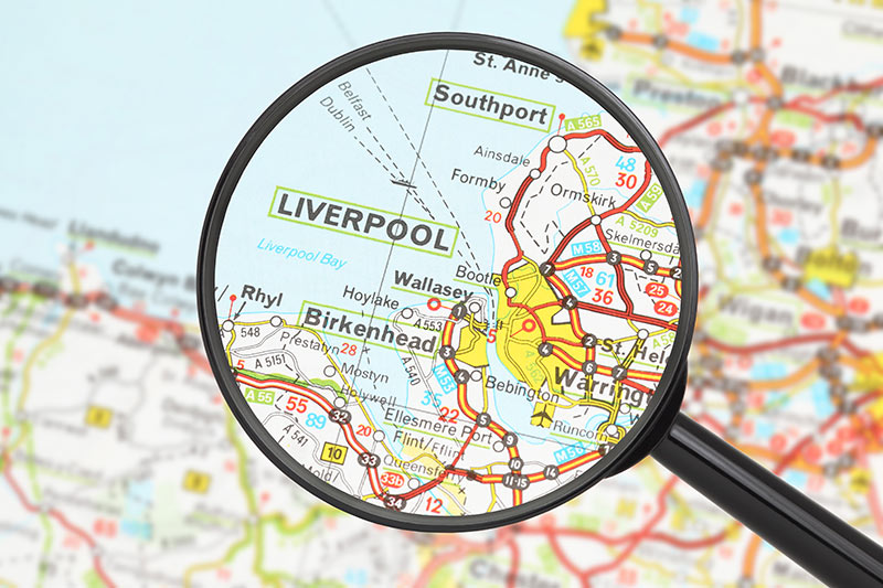 A magnifying glass over a map highlighting Liverpool