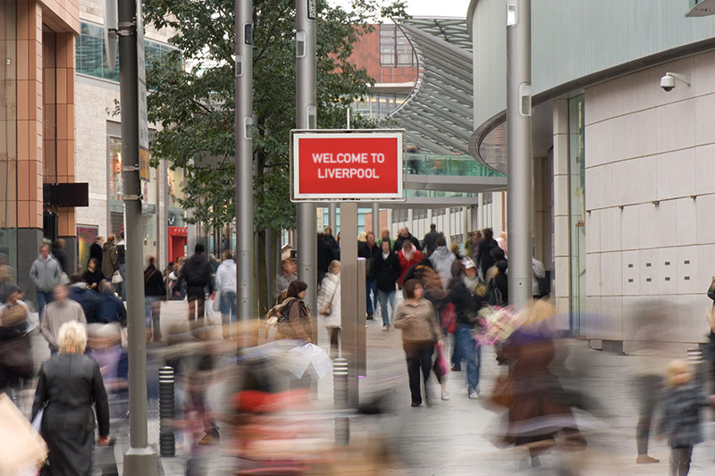 A busy street with a sign that reads welcome to Liverpool