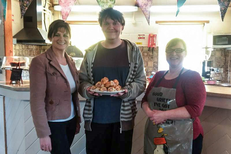 A group of 3 adults standing in a kitchen, the man in the middle holding a plate of cakes