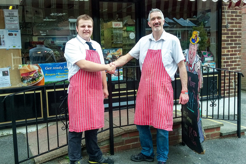 Two men stood, wearing aprons, shaking hands