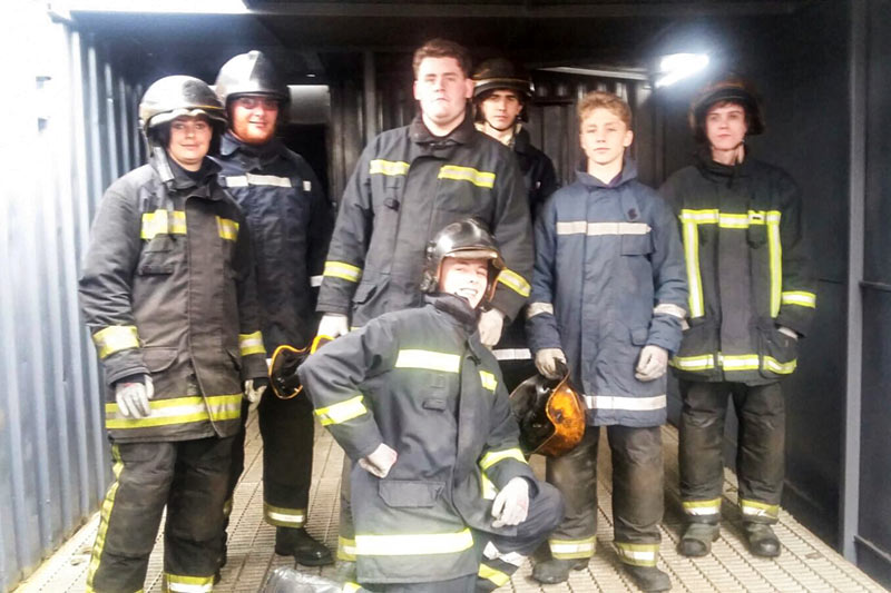 A group of young adults stood, wearing firefighter suits/gear