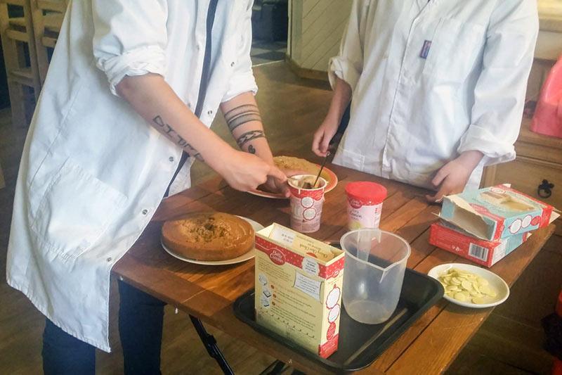 2 people stood at a table preparing baking ingredients