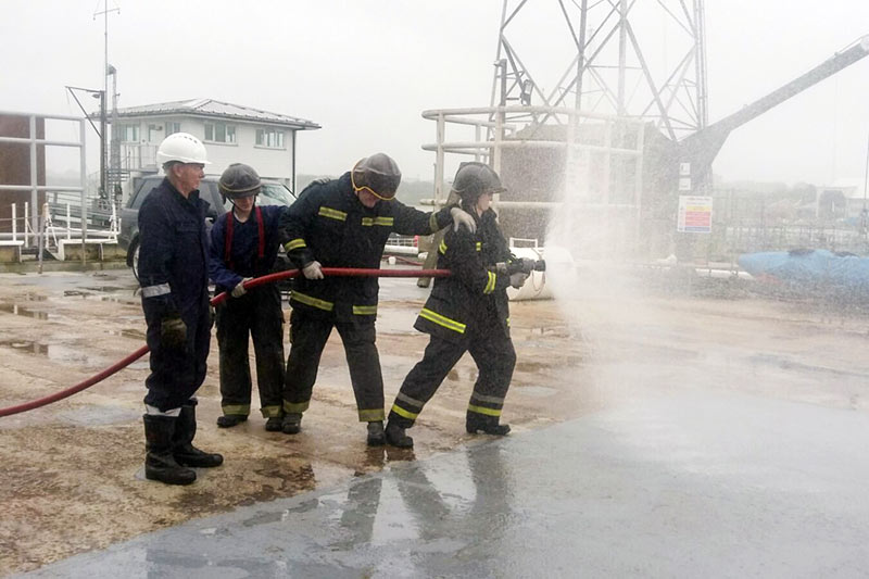 four firefighters holding a hose shooting water