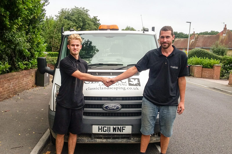 Two men stood in front of a work van shaking hands