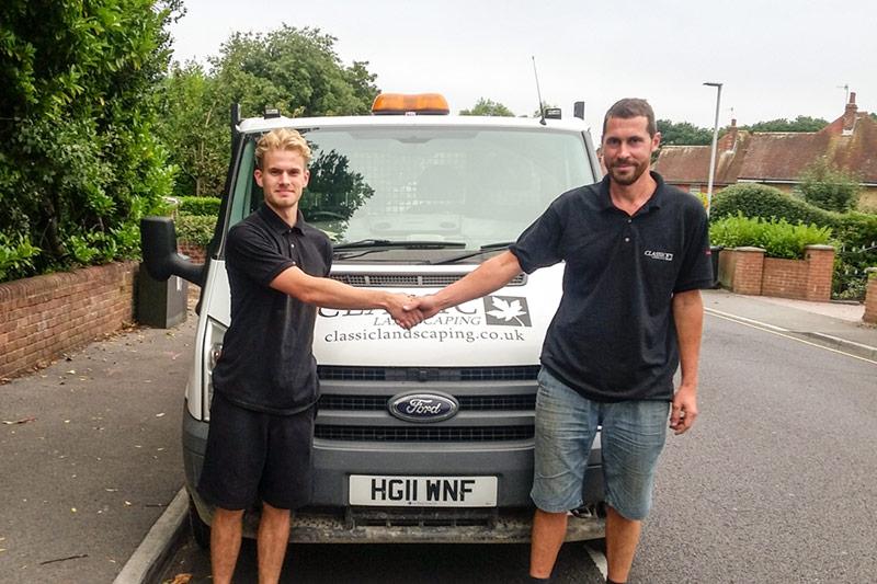 Two men stood in front of a work van shaking hands